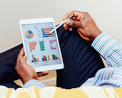 A man's legs and hands, holding a tablet displaying graphs and charts