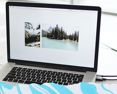Laptop displaying a picture of a lake with pine trees