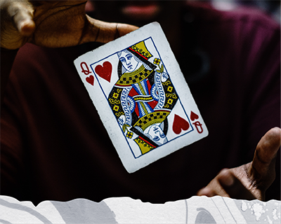 The hands of a magician with the Queen of Hearts card floating between them.
