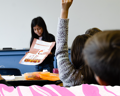 A girl presenting a project in class. In the foreground, the back of two children's heads.