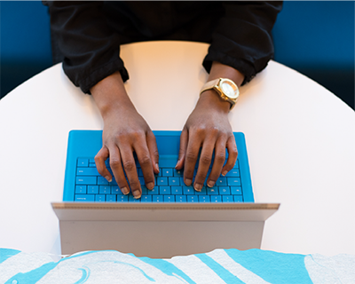 The hands of someone wearing a gold watch typing on a blue laptop keyboard