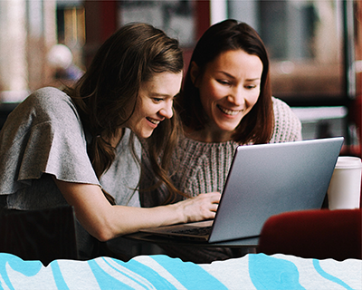 Two women smiling looking at a laptop screen
